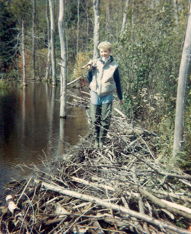 woman carrying a fishing  rod and walking along a Beaver Dam, Opeongo, Ontario in the eighties.