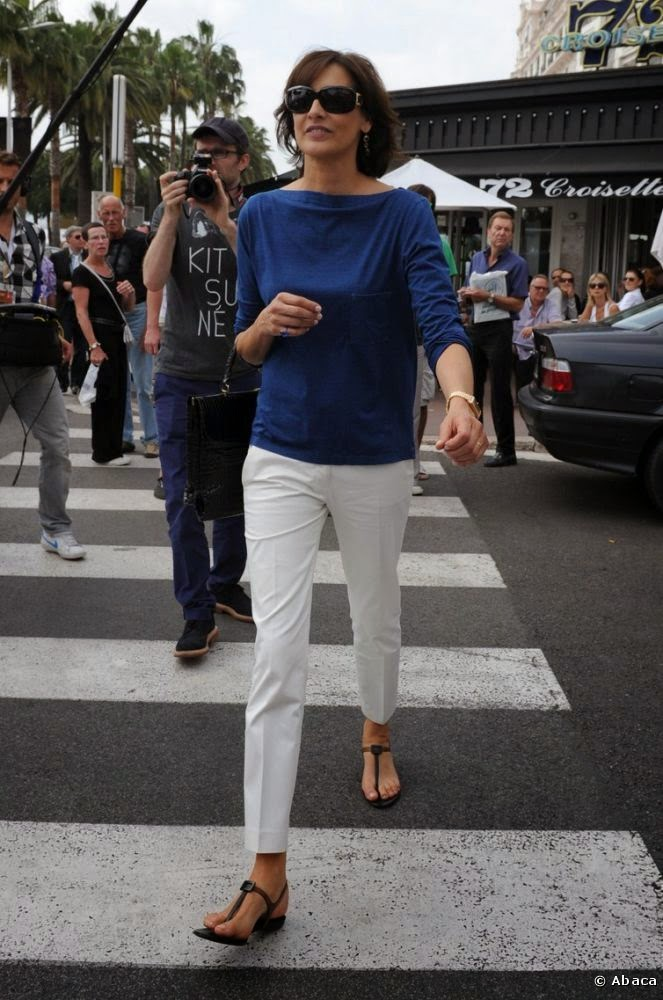 Ines de la Fressange in chic white pants, sweater and flat sandals.