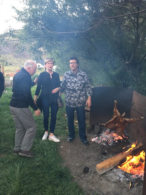 two men and a woman standing in front of a cooking fire