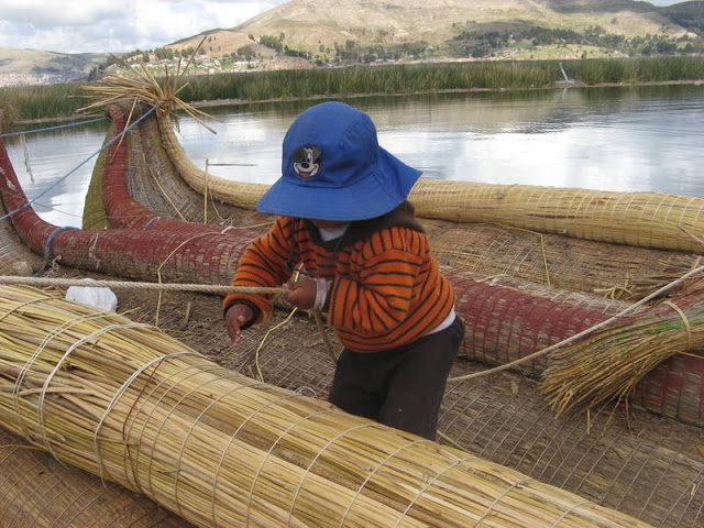 small boy helps his father with a straw boat on Uros Island, Peru