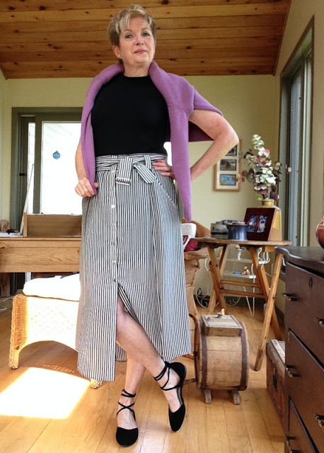 woman in striped midi-skirt, black flats, and tee shirt with pink sweater over her shoulders