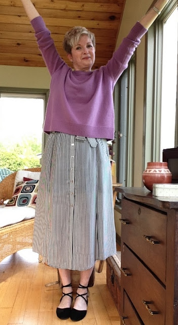 woman in striped midi-skirt, pink sweater, and black flats, holding arms up in the air