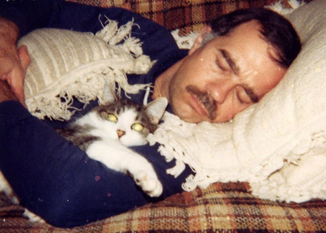 Man and cat napping together.