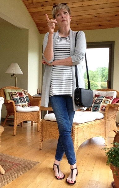 woman in jeans, tank and cardigan, pointing finger assertively