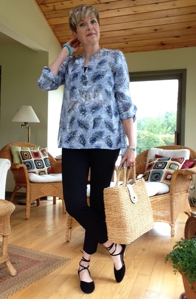 Woman in blue tunic, black pants, black flats with a straw tote bag