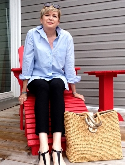 Women sitting on a red Arirondack chair wearing black pants, black sandals, and a blue shirt.