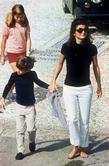woman in white jeans, black tee, and sunglasses holding the hand of her son