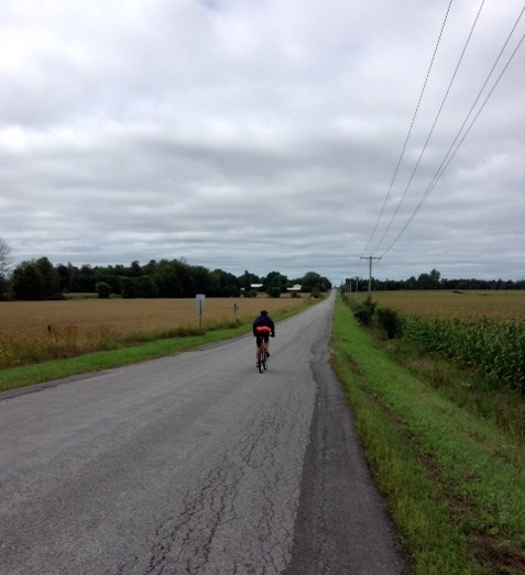 Man on a bike on a country road.
