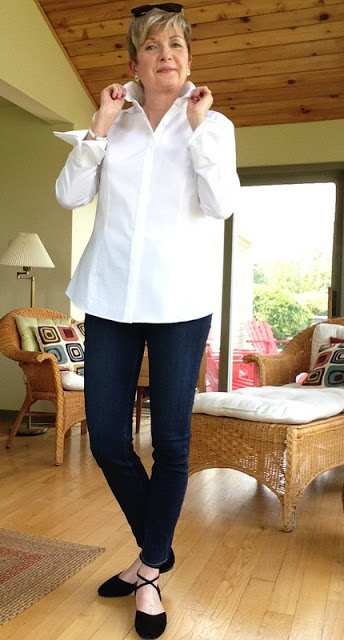 woman in white shirt, jeans, black flats holding collar of shirt