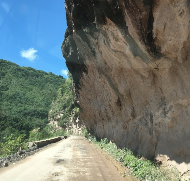 narrow gravel road with large overhanging cliff, near Salta Argentina