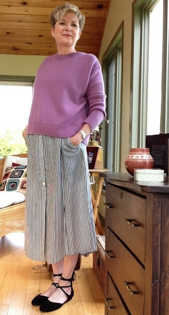 Woman in pink sweater, striped skirt with hands in pockets.