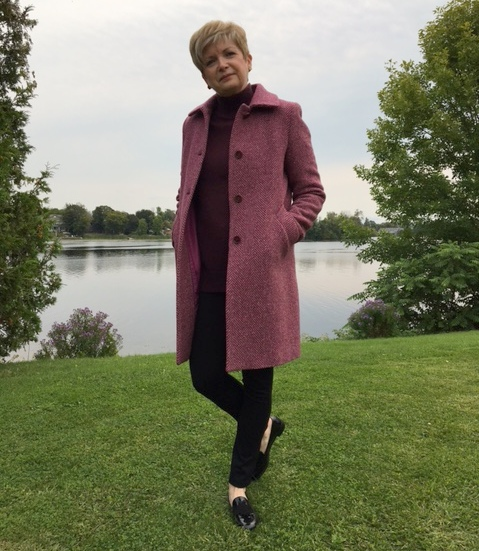 woman in tweed coat and slacks standing in front of water