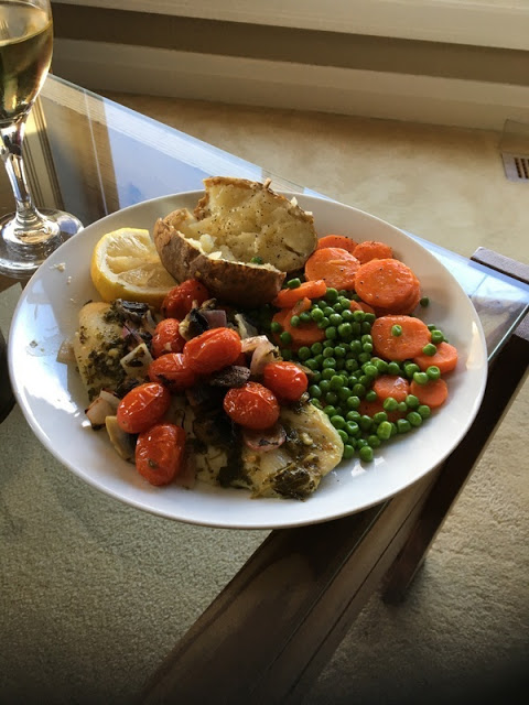 tilapia with tomatoes, mushrooms and olives, baked potato, and carrots and peas