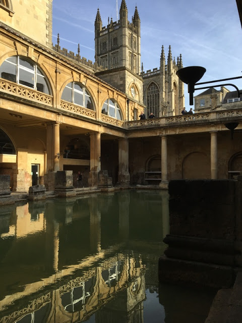 pool at a Roman Bath, with Bath Abbey in the background