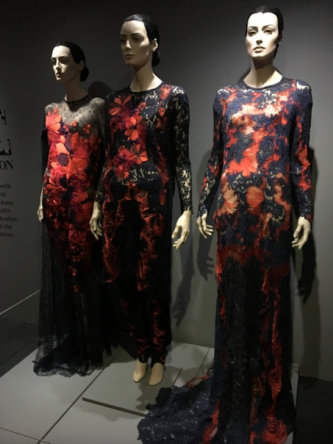 three mannequins in red and blue lace gowns