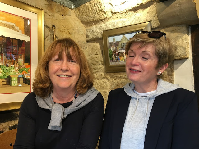 two women in a cafe with stone walls