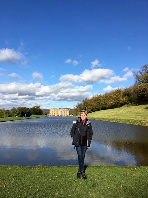 woman standing beside a lake with Chatsworth House in the background