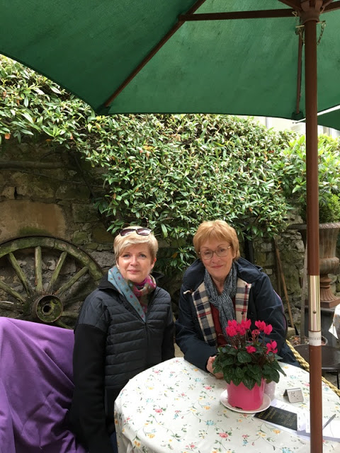 two ladies in sweaters and scarves at an outdoor cafe table, under a green umbrella