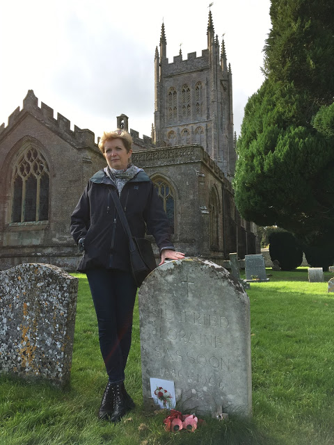 woman in churchyard beside a gravestone