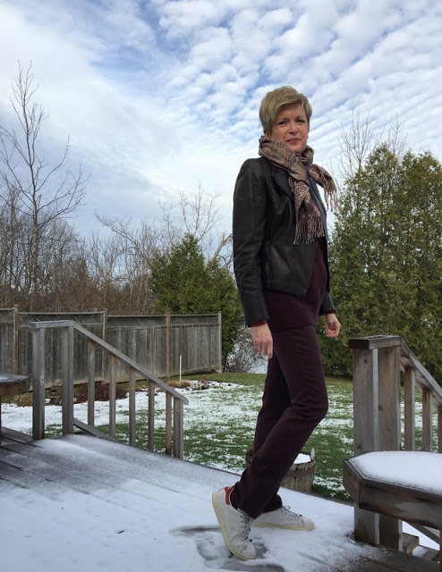 woman standing on snow covered deck in burgundy sweater and jeans and leather jacket