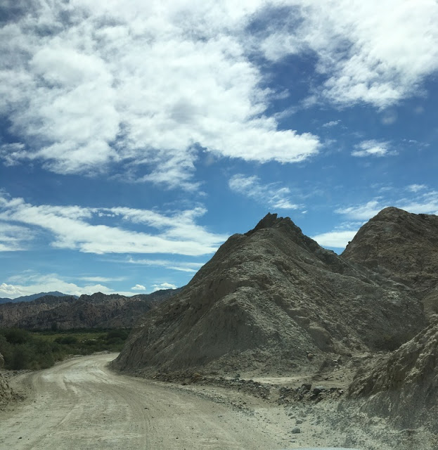 gravel road twists around sharp rocky peaks