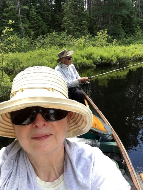 woman and man in hats and sunglasses fishing from a canoe