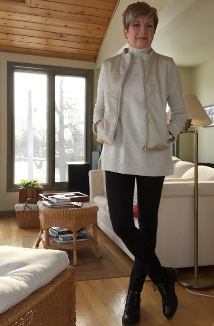 smiling woman in cream vest and sweater, black leggings and boots in a room with hardwood floor and ceiling