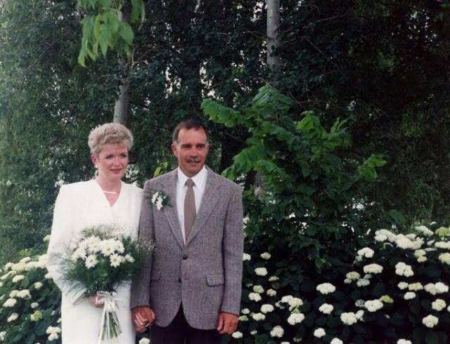 woman in white suit and a bridal bouquet, holding hands with man in jacket and tie