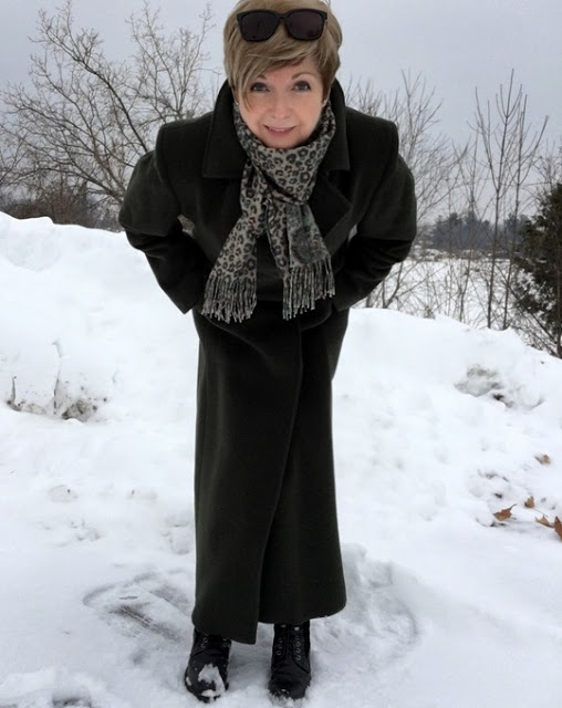 woman in coat and scarf, leaning down to smile into camera