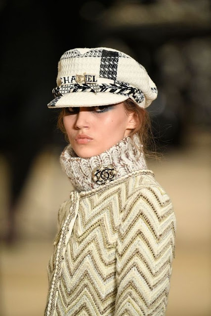 model in a cream sweater and a cream newsboy hat