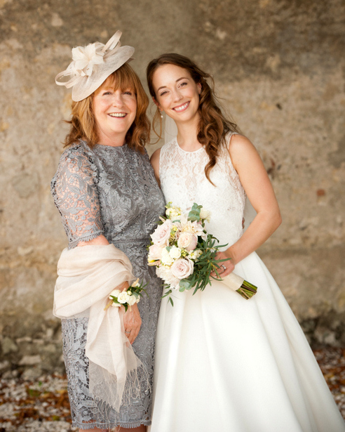 woman in a cream fascinator, grey lace dress and cream shawl, with young woman in a wedding dress
