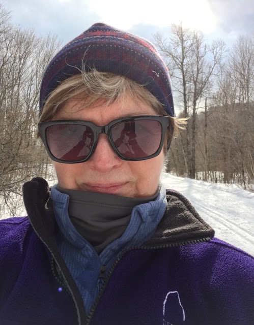 woman in purple ski hat and vest and sunglasses.
