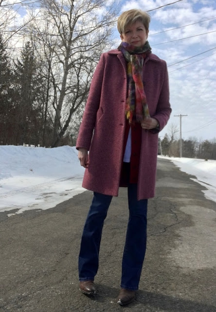 woman in pink tweed coat, scarf, and jeans