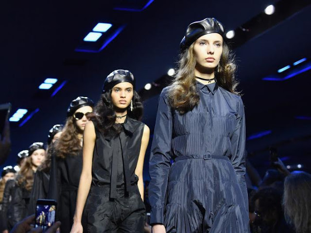 models in blue outfits and black leather berets