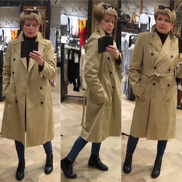 woman in a trench coat, jeans, and turtleneck taking selfies in a store