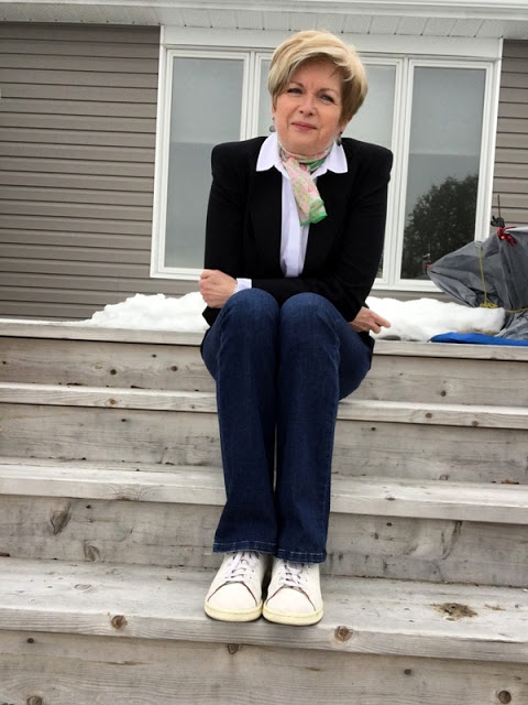 woman sitting on steps in a blue jacket and jeans and white shirt and sneakers.