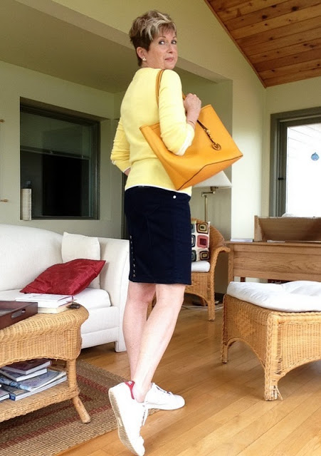 woman in yellow sweater and blue denim skirt