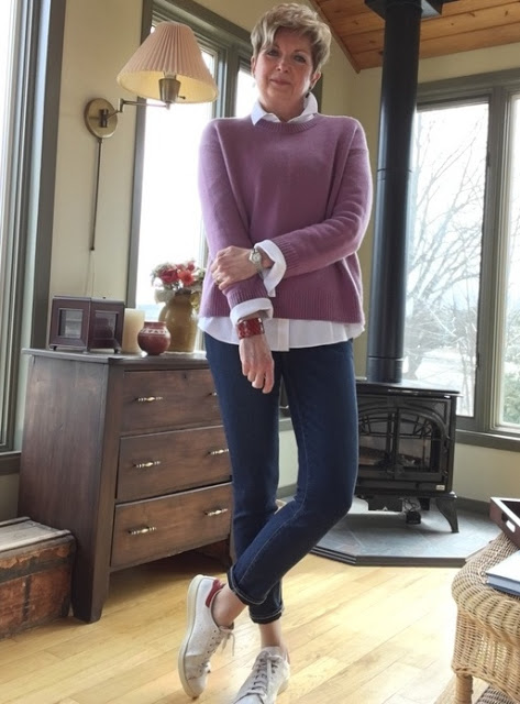 woman in pink sweater, jeans, and sneakers