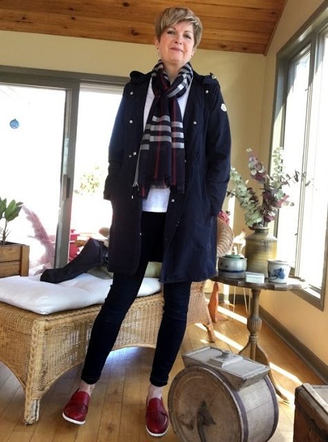 woman in navy coat, jeans, white tee, plaid scarf, and red shoes