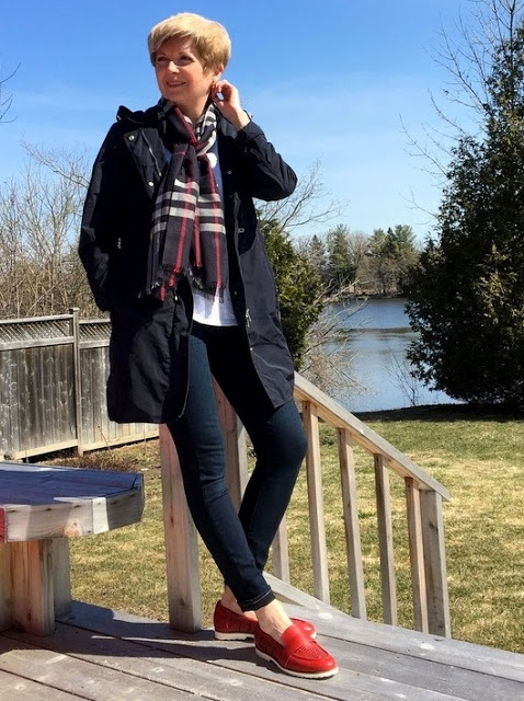 woman in navy coat, jeans, white tee, plaid scarf, and red shoes standing on a deck