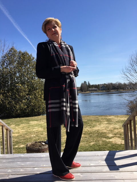 woman in a blue suit, plaid scarf, and red shoes standing on a deck