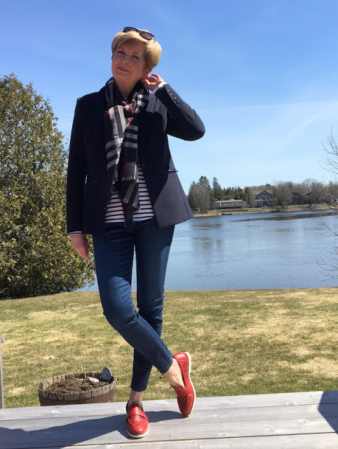 woman in navy jacket, striped tee, plaid scarf, jeans and red shoes standing on a deck