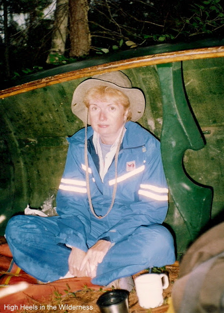 woman in blue rain suit and Tilly hat sitting under upturned canoe