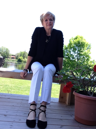 woman in black jacket, white jeans, and black flats sitting on a deck bench.