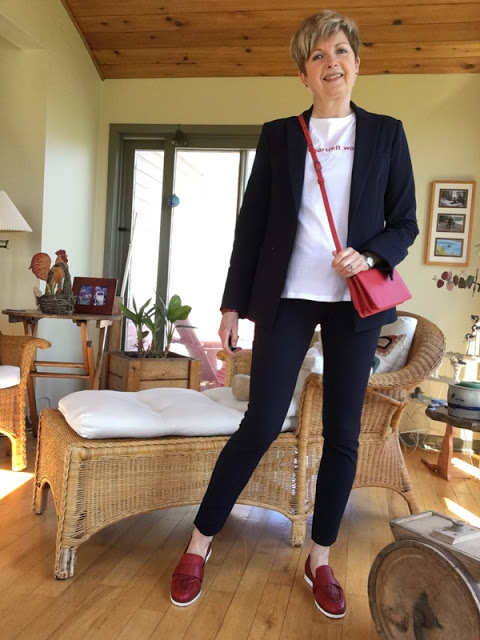 woman in navy suit, white tee, red shoes and red bag