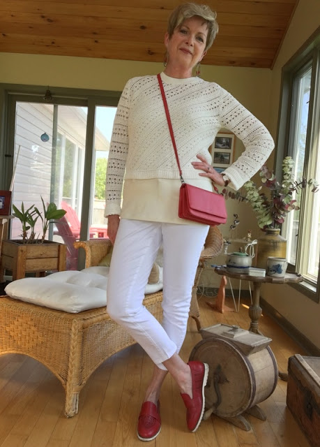 woman in white sweater, white jeans, red shoes, and red bag