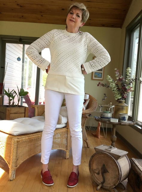 woman in white sweater, white jeans, and red loafers
