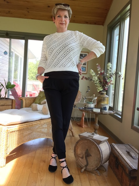 woman in black pants, black flats, and cream crocheted sweater.