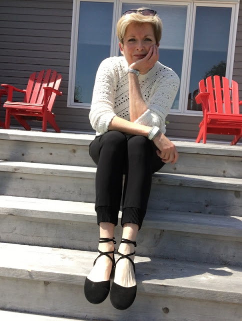 woman sitting on steps in black pants, shoes and while crocheted sweater
