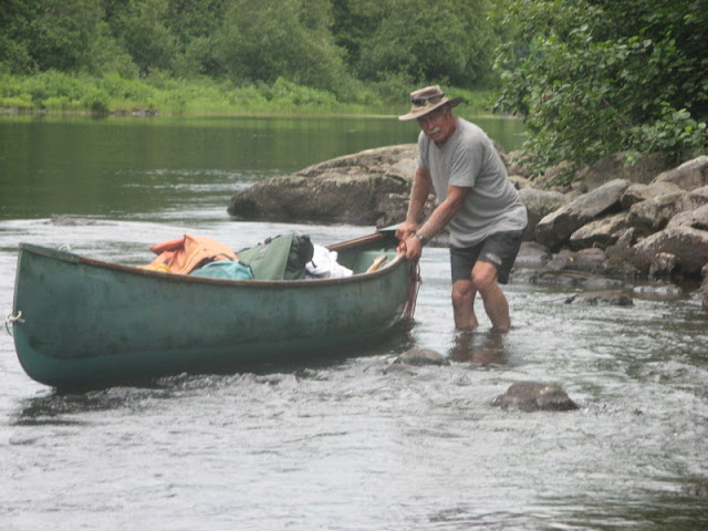 man wading through water and guiding a canoe